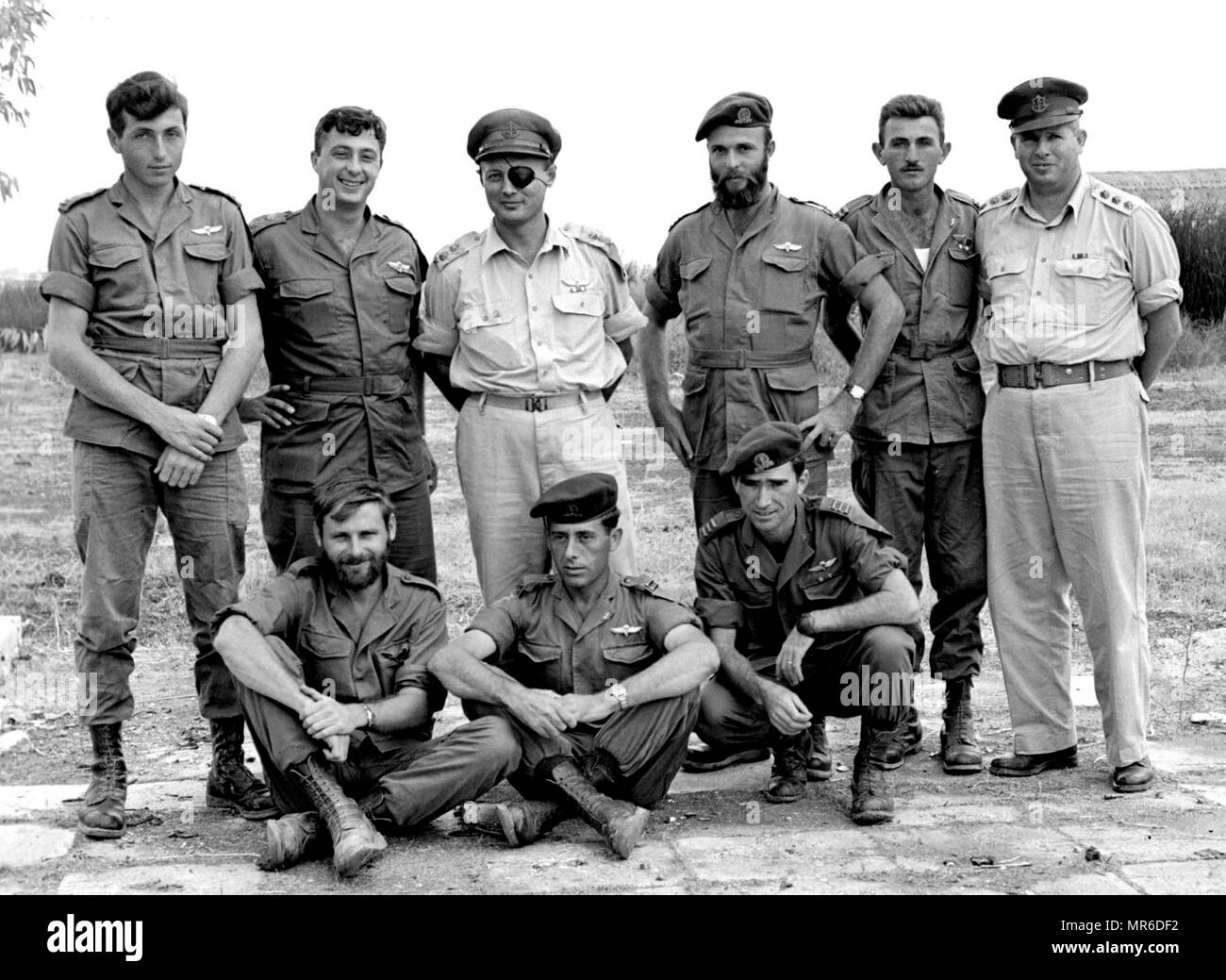 Operation Egged (the Kuntilla operation), was an Israeli military operation carried out on night of October 28–29, 1955 that targeted an Egyptian military post at Kuntilla, located in north-eastern Sinai. Israeli commanders pose after Operation Egged. Standing left to right: Lt. Meir Har-Zion, Maj. Ariel Sharon, Lt. Gen. Moshe Dayan, Capt. Danny Matt, Lt. Moshe Efron, Col. Asaf Simhoni; on ground, l to r: Capt. Aharon Davidi, Lt. Yaakov Yaakov, Capt. Rafael Eitan - Stock Image
