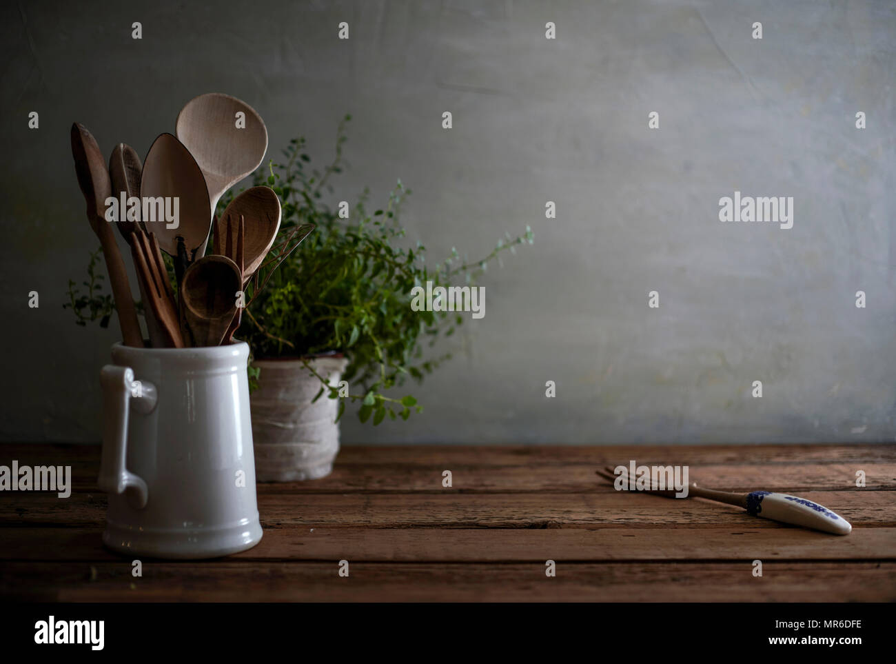 A still life image of a rustic, wood kitchen counter with wooden spoons in a porcelain vessel and a lovely, tangled oregano plant in the background. - Stock Image