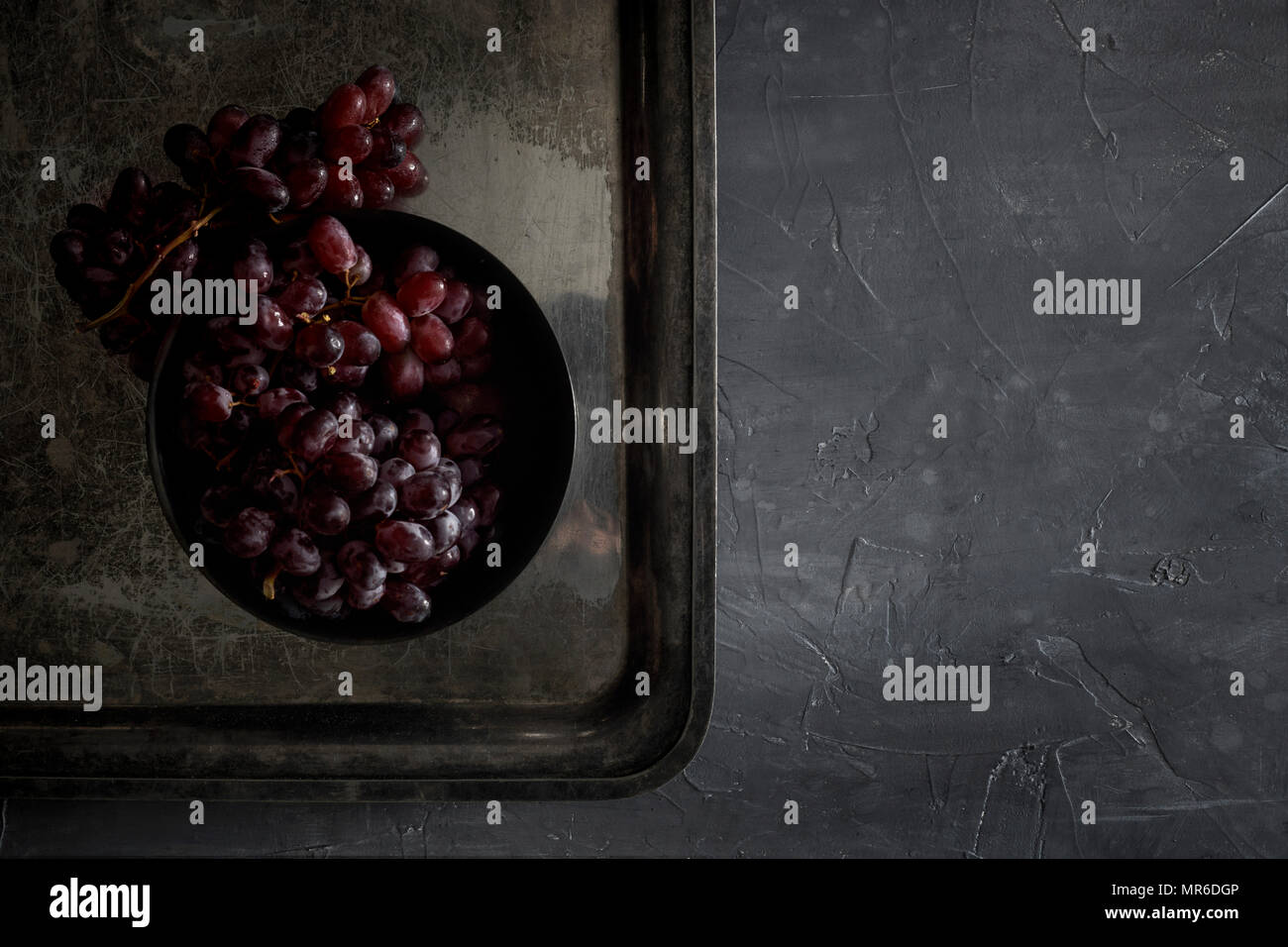 Fresh, red grapes in on a patinated metal tray on a dark countertop. Dark, moody, natural lighting. - Stock Image