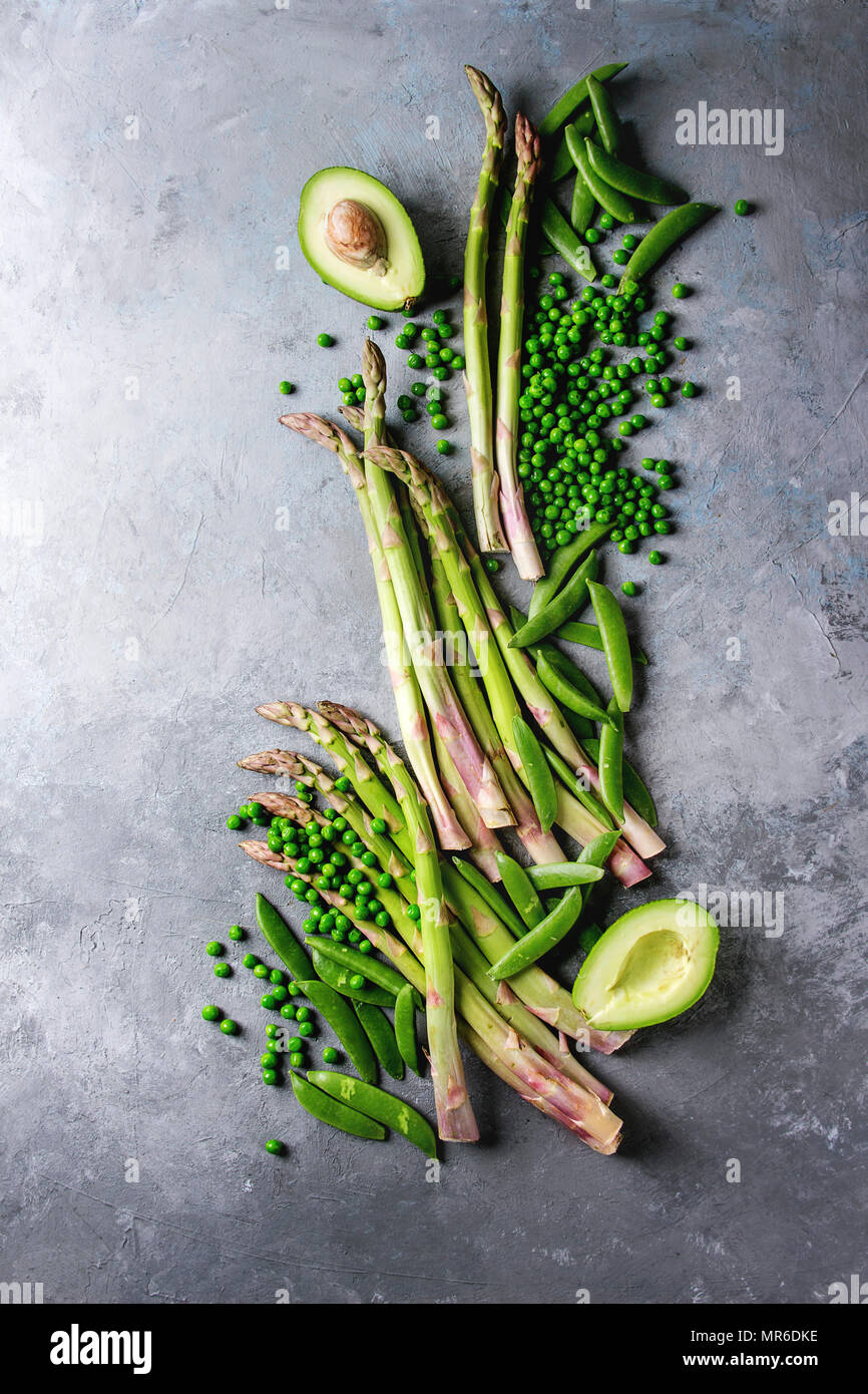 Variety of raw uncooked organic young green vegetables asparagus, peas, pod pea, avocado over grey texture background. Top view, copy space. Healthy e Stock Photo