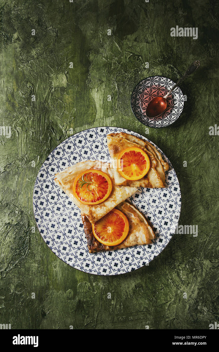 Homemade crepes pancakes served in white decorate ceramic plate with bloody oranges and rosemary syrup with sliced sicilian red oranges over green tex - Stock Image