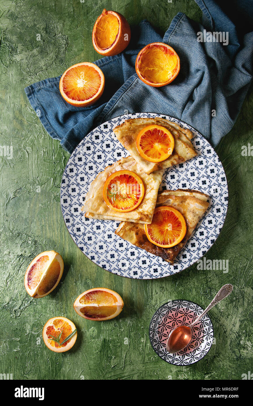 Homemade crepes pancakes served in white decorate ceramic plate with bloody oranges and rosemary syrup with sliced sicilian red oranges and blue cloth - Stock Image