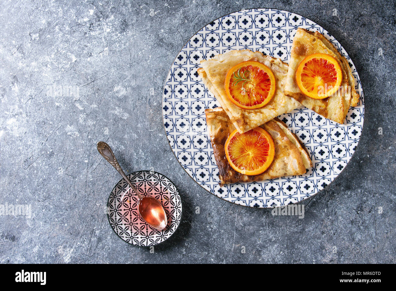 Homemade crepes pancakes served in white decorate ceramic plate with bloody oranges and rosemary syrup with sliced sicilian red oranges over blue text - Stock Image