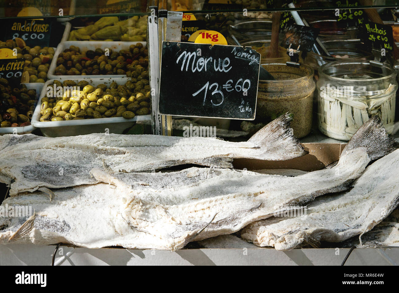 Market stall with dry salted cod fish and vegetables at Parisian street farmers market. - Stock Image