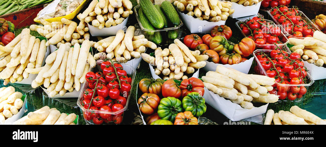 Market stall with fresh spring season vegetables at Parisian street farmers market. White asparagus, tomatoes, cucumbers. - Stock Image
