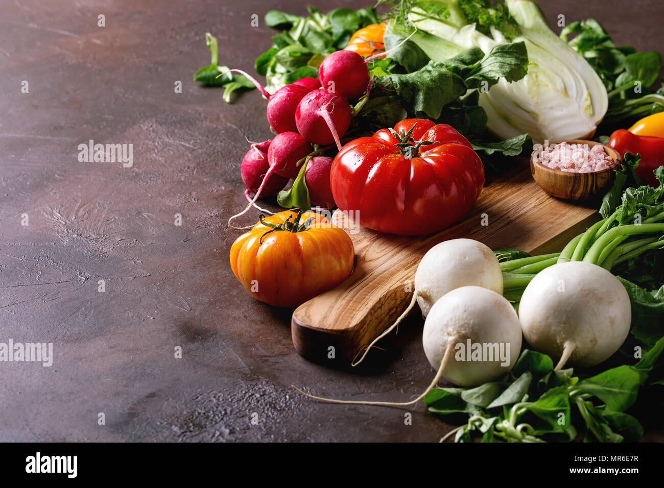 Variety of wet raw fresh organic colorful vegetables tomatoes, radish with leaves, fennel, paprika, salt for salad on wooden chopping board over dark  Stock Photo