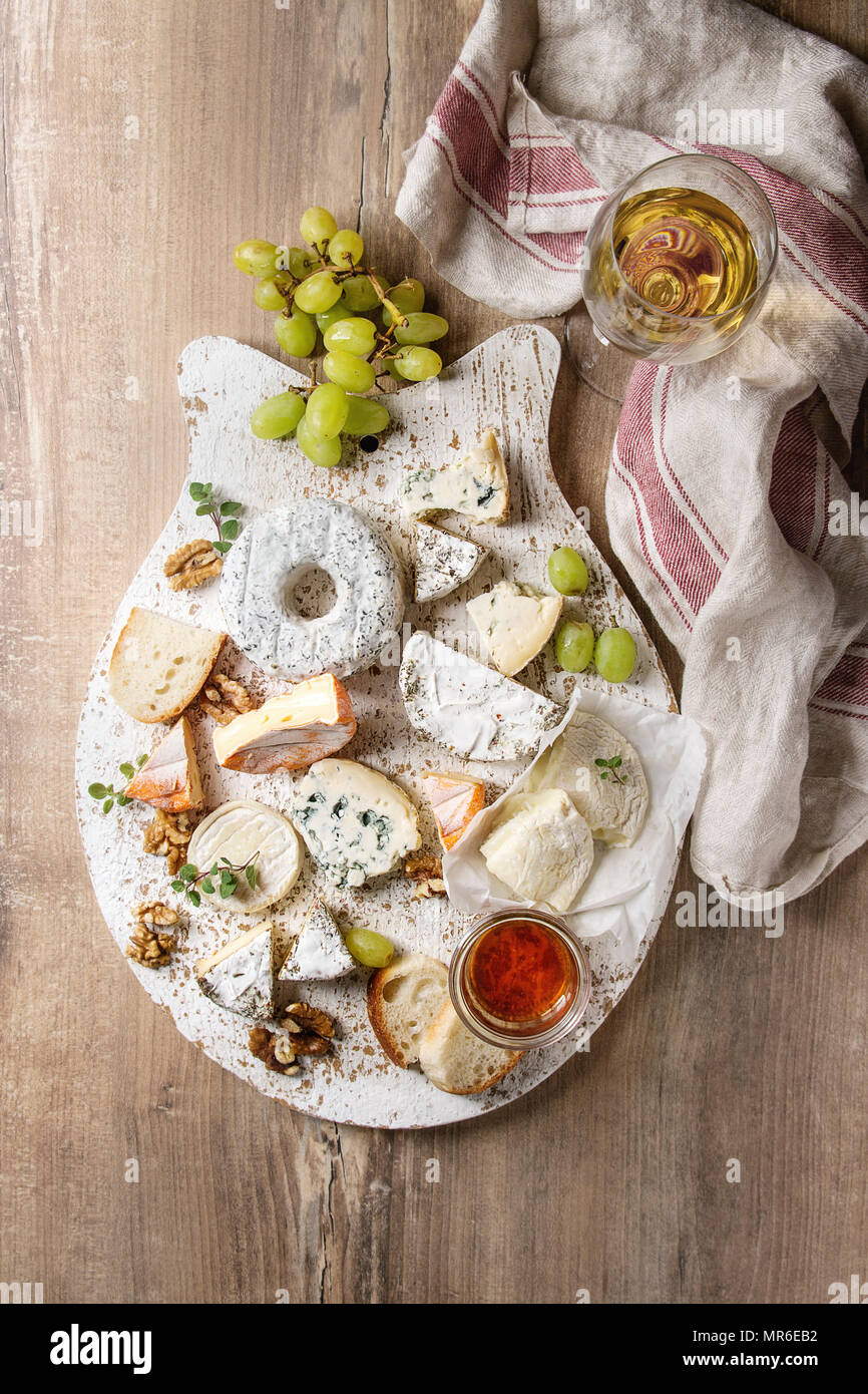 Cheese plate assortment of french cheese served with honey walnuts bread and grapes on white wooden serving board over wood texture background. Top & Cheese plate assortment of french cheese served with honey walnuts ...