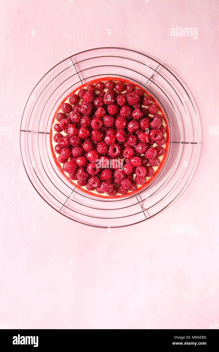 Red raspberry shortbread tart with lemon custard and glazed fresh raspberries served on cooling rack over pink pastel background. Top view, copy space - Stock Image