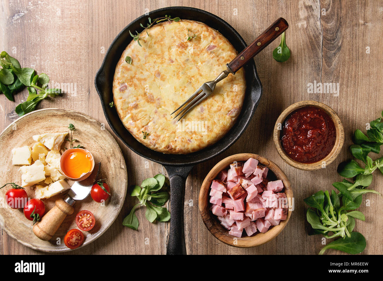 Spanish potato omelette tortilla with bacon served in cast-iron pan with sauce and ingredients above over wooden background. Top view, space. - Stock Image