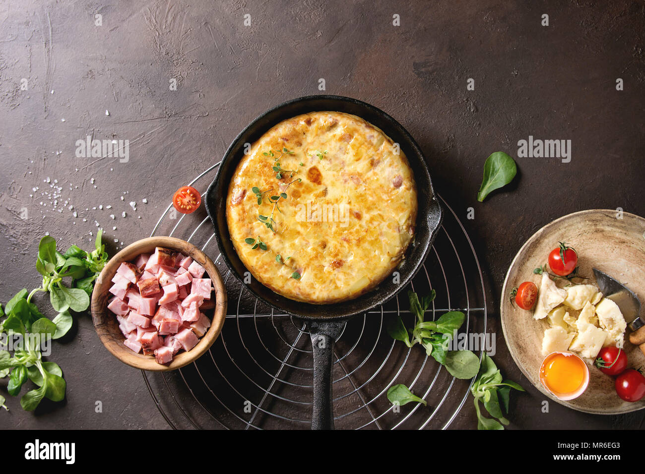 Spanish potato omelette tortilla with bacon served in cast-iron pan on cooling rack with ingredients above over over dark brown texture background. To - Stock Image