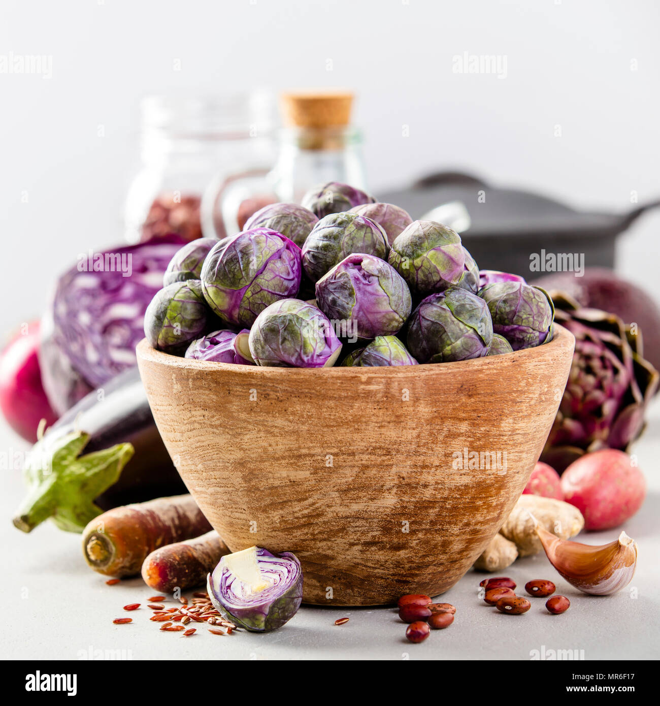 Purple Brussels sprouts in a bowl and healthy ingredients on concrete background. Vegan, gluten free, allergy-friendly, clean eating or raw diet. Spac - Stock Image