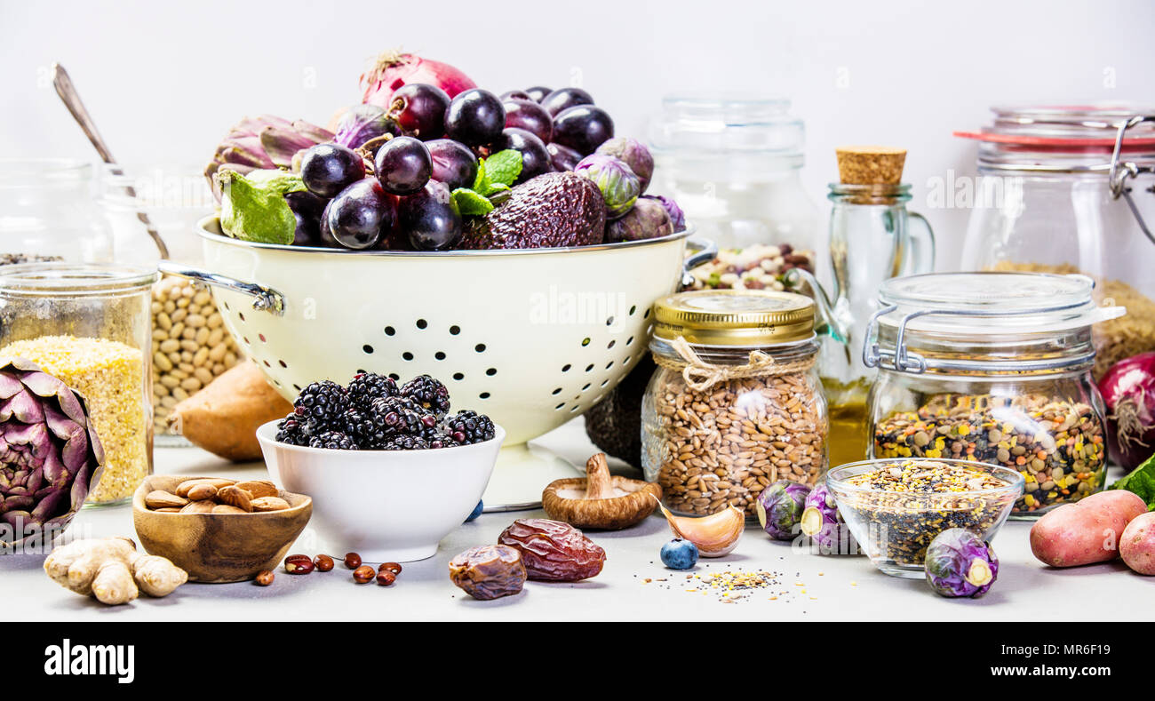 Balanced diet, cooking, vegetarian, raw and clean eating concept - close up of fresh organic fruits and vegetables, grains, legumes and nuts on concre - Stock Image