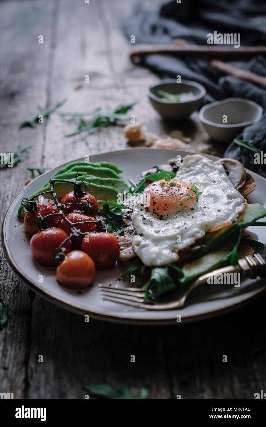 Egg and sliced avocado on toast, set on a rustic kitchen table Stock Photo