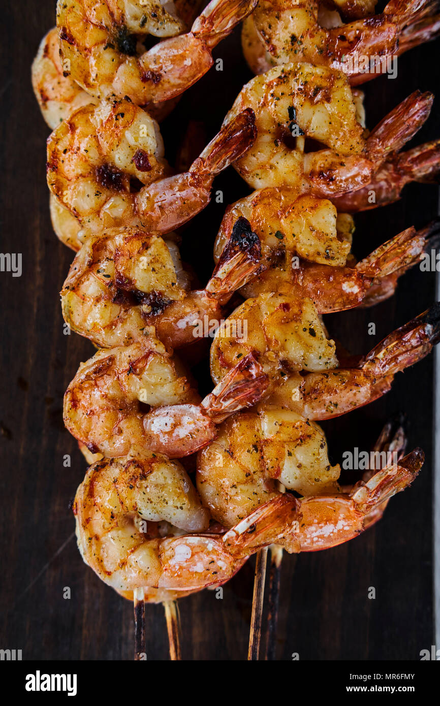 High angle view of plate of grilled shrimp on skewers cooling by the side of the barbecue - Stock Image
