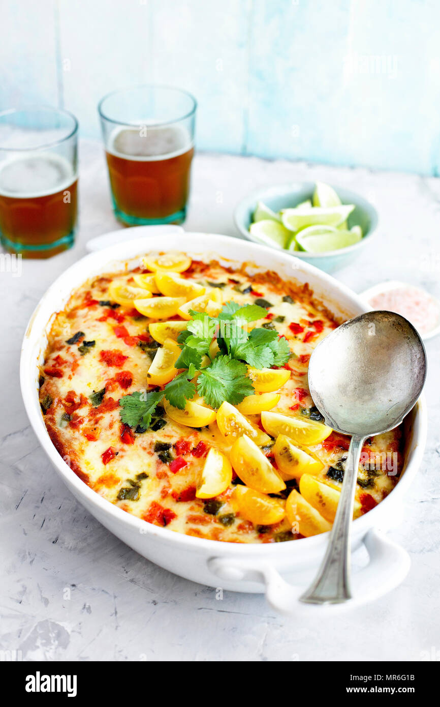 Spaghetti Squash Enchilada Casserole served with Cilantro Salsa and Beer. Photographed on a light grey background. Stock Photo