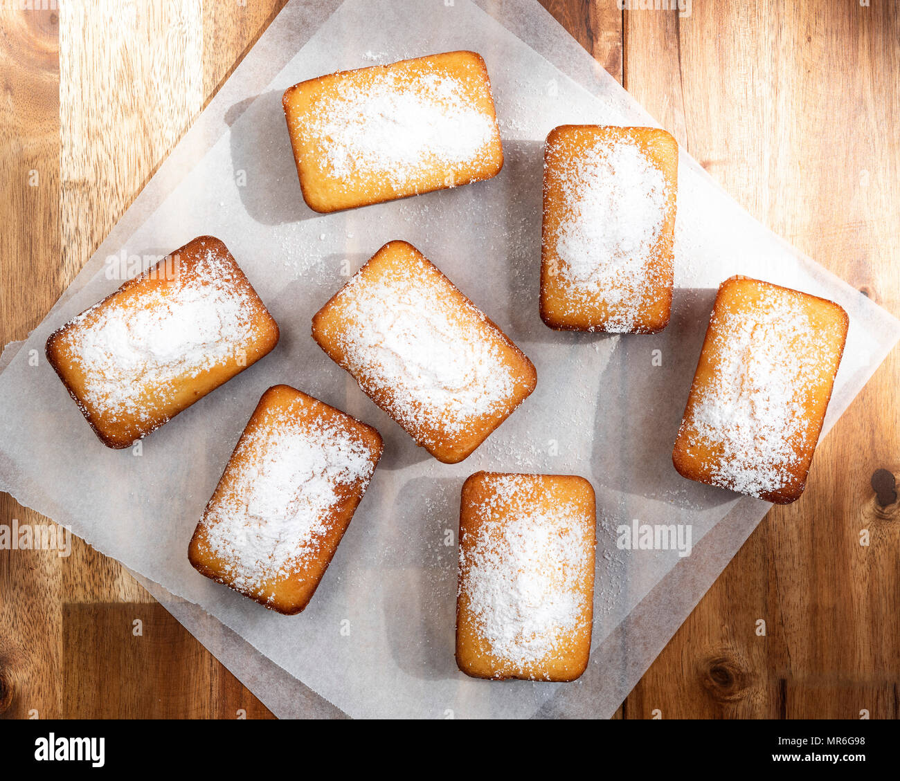 Small orange loaf cakes dusted with icing sugar on baking paper. - Stock Image