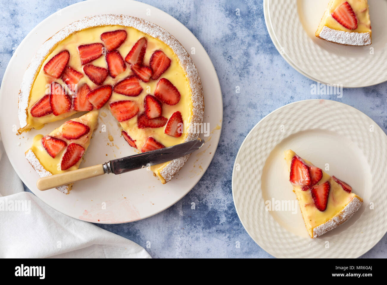 Strawberry Custard dessert cake with a knife and two serves on cake on plates. - Stock Image