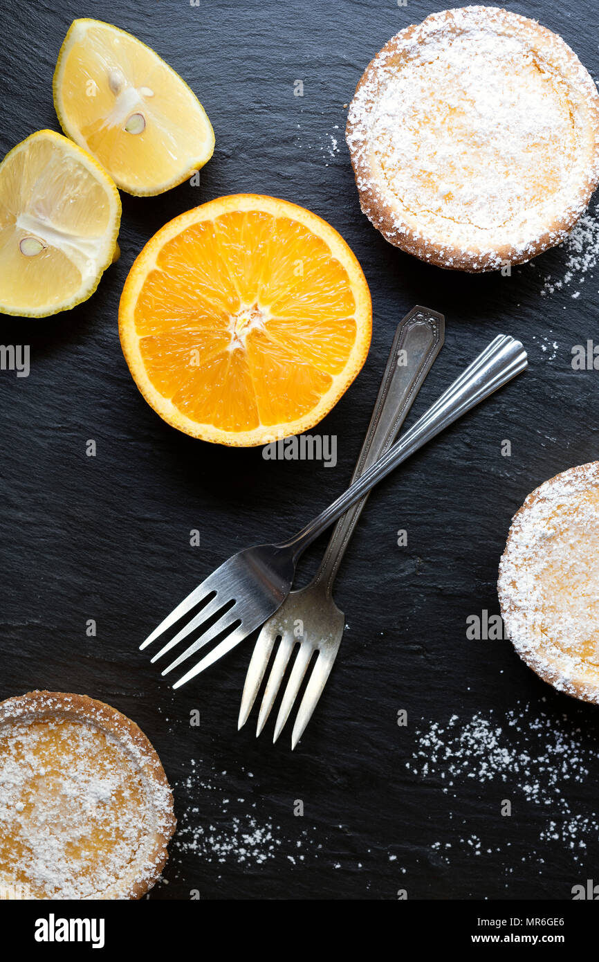 Lemon tarts dusted with powdered sugar, two forks, half an orange and lemon pieces. - Stock Image