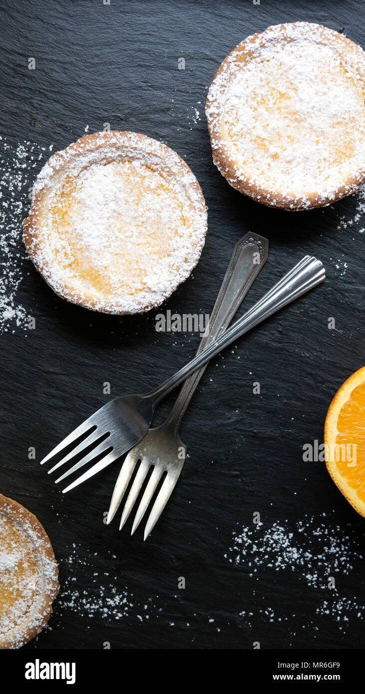 Two lemon tarts dusted with powdered sugar and two forks. - Stock Image