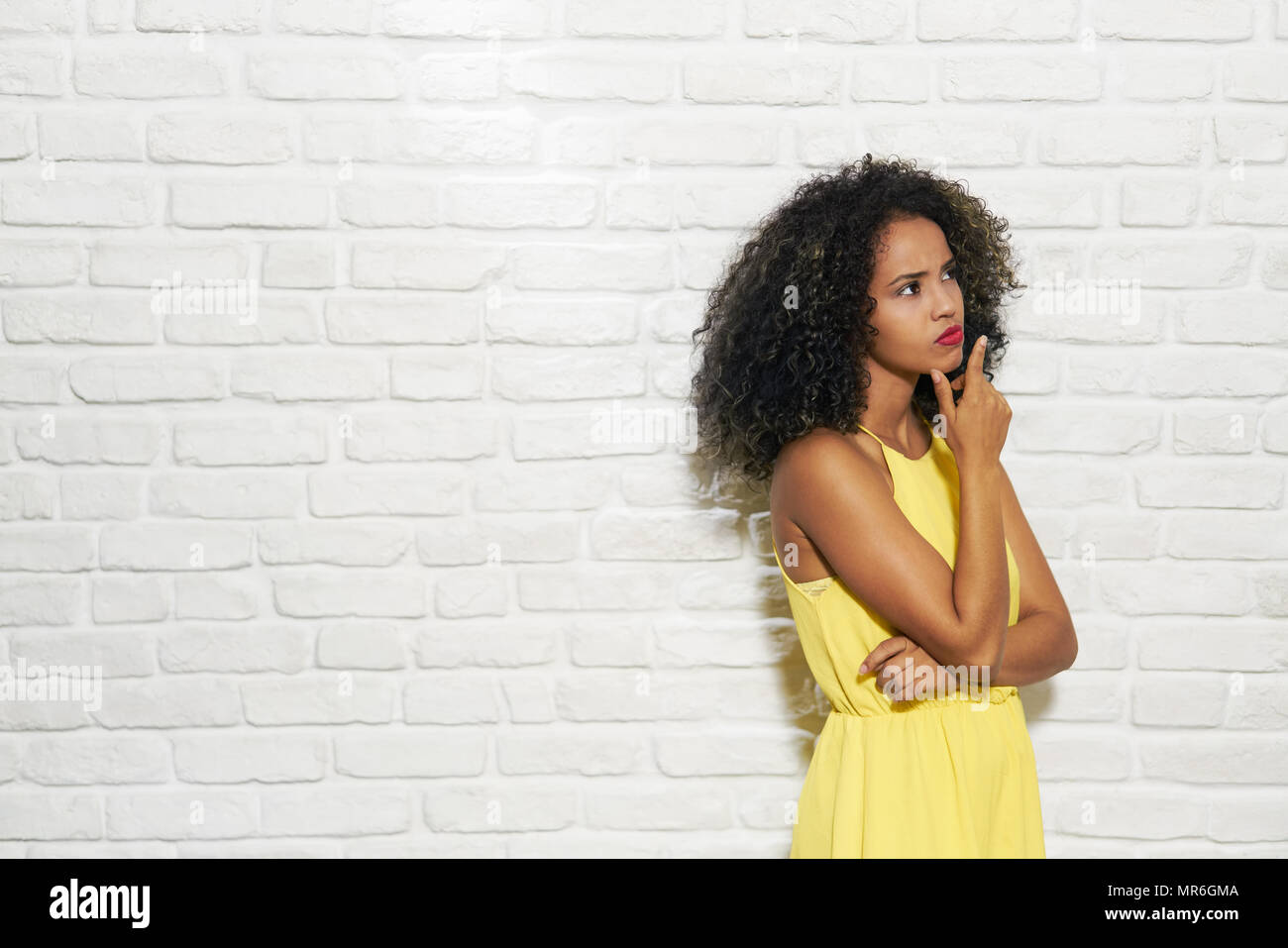 Portrait of puzzled woman having doubts, doubtful black girl thinking. Copy space - Stock Image