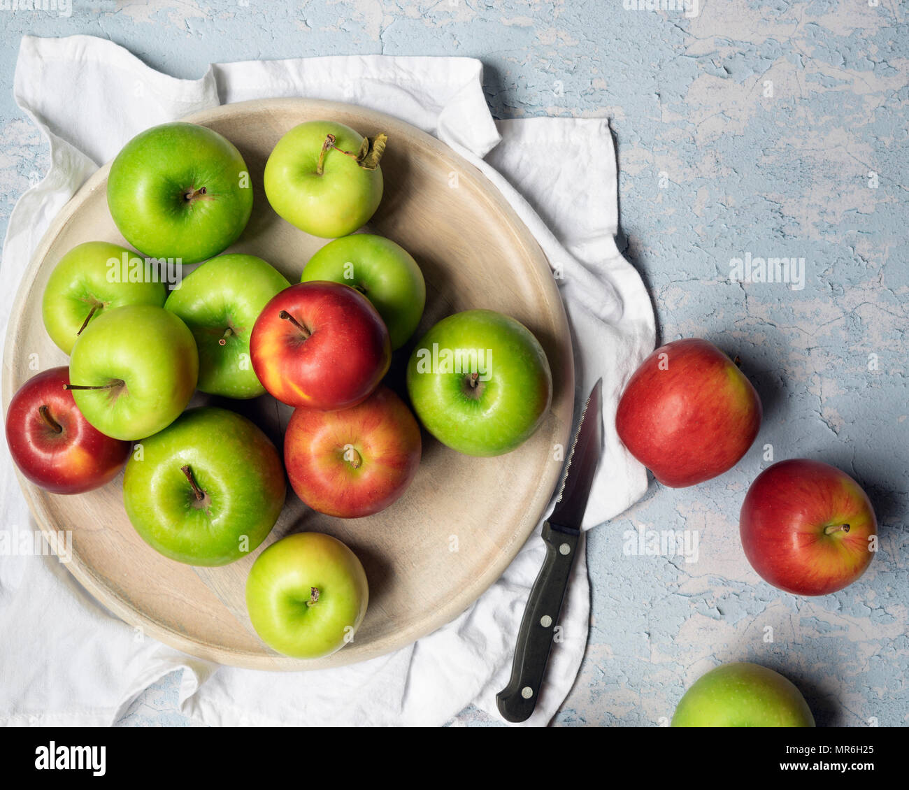 Green cooking apples and red eating apples with a knife against a blue textured background. - Stock Image