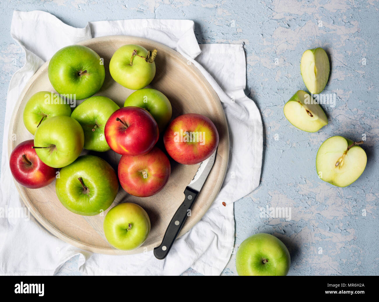 Green cooking apples and red eating apples with a knife on a round wooden board. - Stock Image