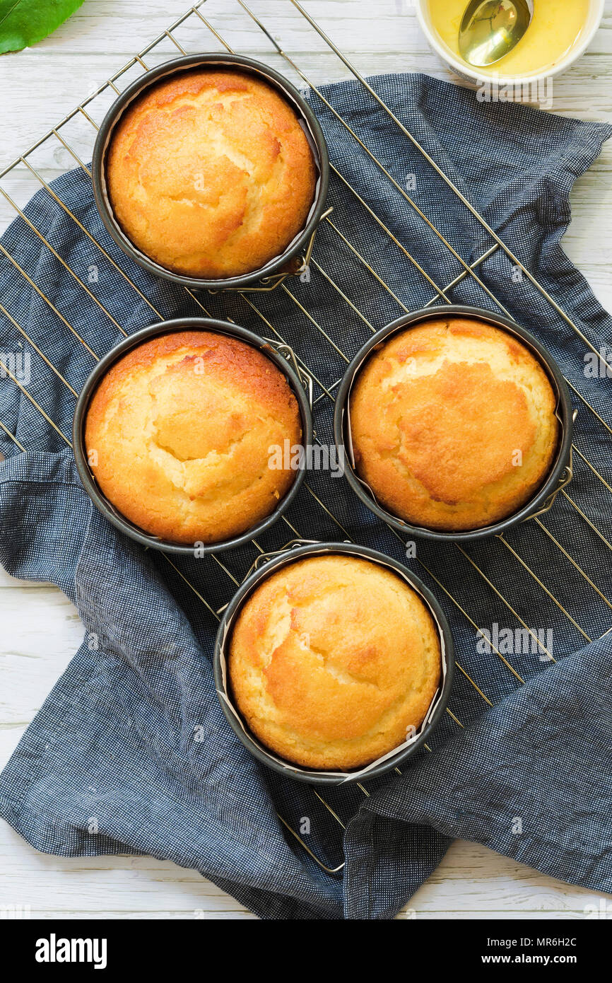 Small round individual orange cakes cooling in cake tins on a wire rack and blue cloth napkin. - Stock Image