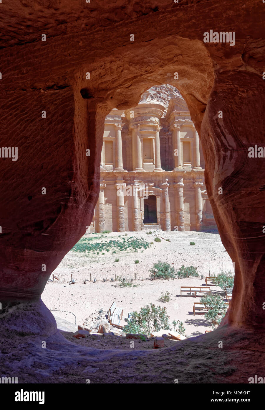 View through the rock window of a storage room in Petra to the monastery Al-deir, Jordan - Stock Image