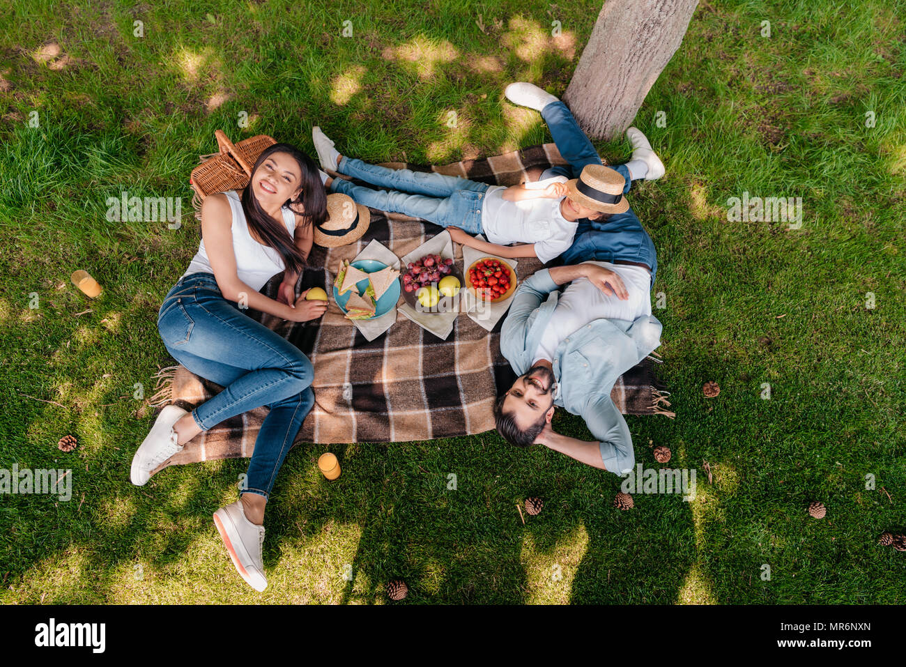 Happy multiethnic family eating and drinking while resting on plaid at picnic - Stock Image