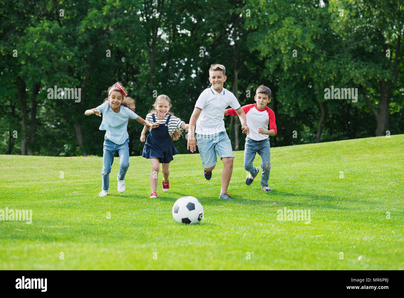 Cute happy multiethnic kids playing soccer with ball in park - Stock Image