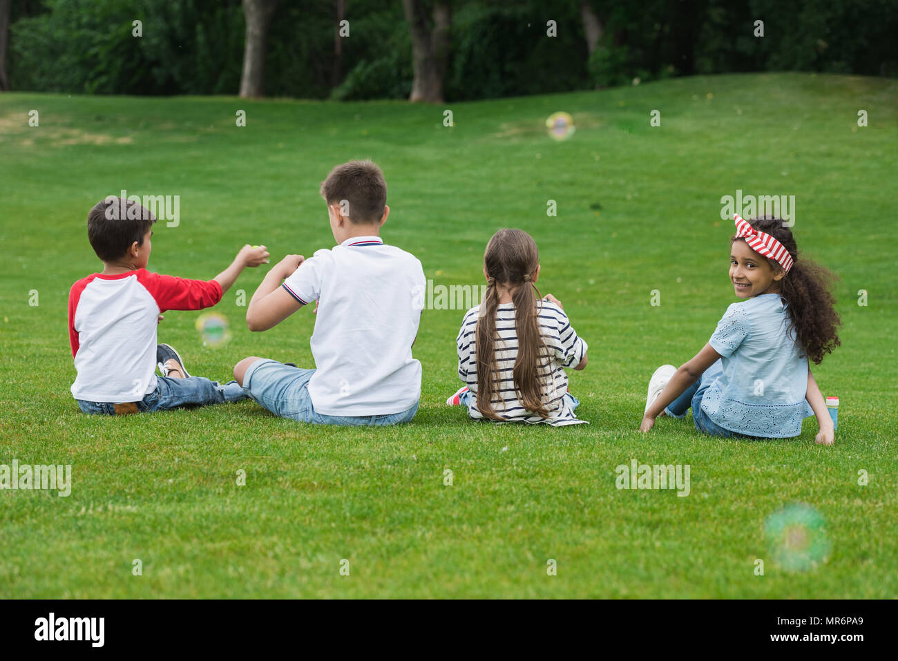 Back view of cute multiethnic kids playing with soap bubbles while sitting on green grass in park - Stock Image