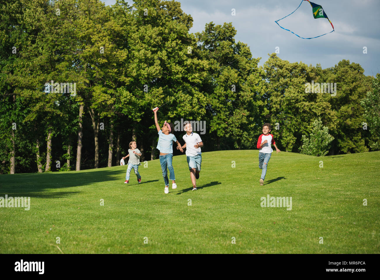 Cheerful multiethnic kids playing together while running with kite in park - Stock Image
