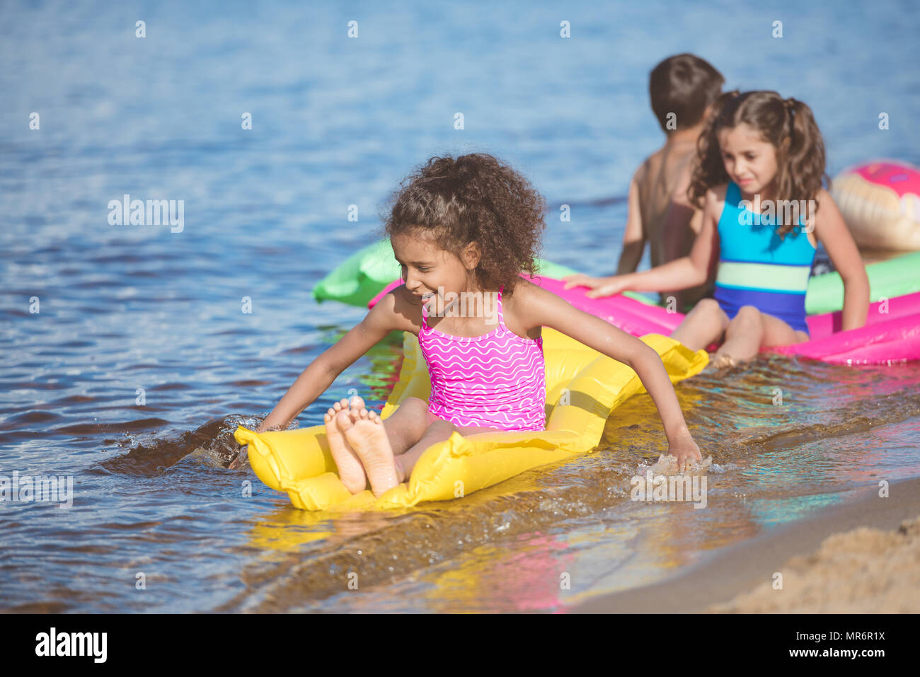 multicultural girls in swimsuits swimming on inflatable mattresses - Stock Image
