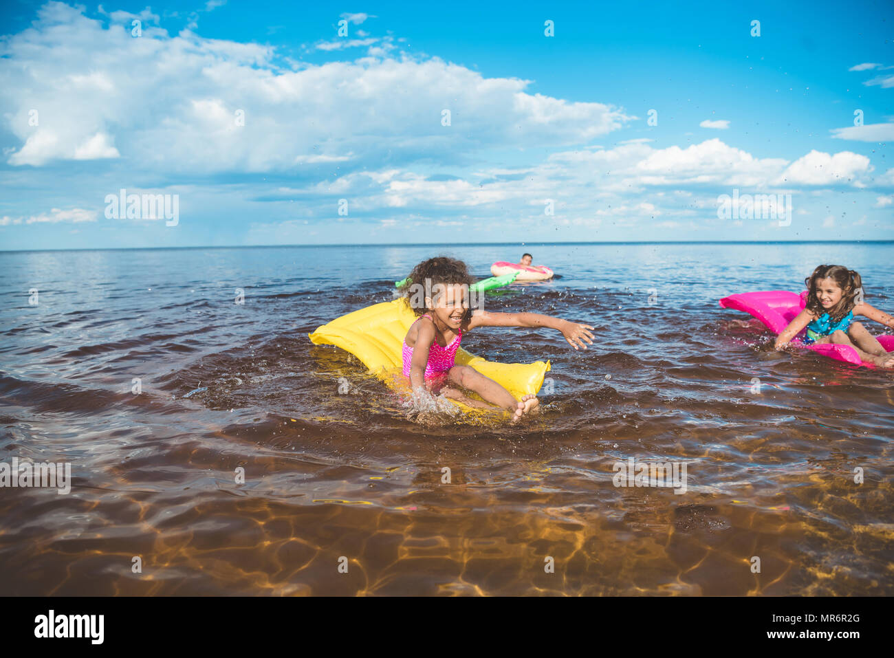 multicultural little girls swimming on inflatable mattresses at sea together - Stock Image