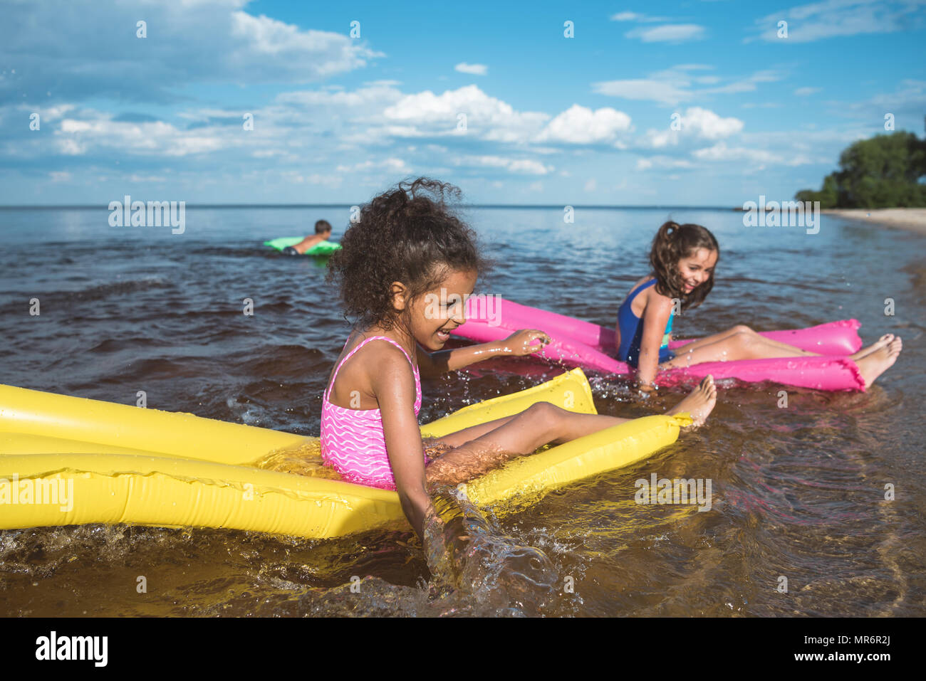 multicultural happy girls swimming together on inflatable mattresses at sea - Stock Image