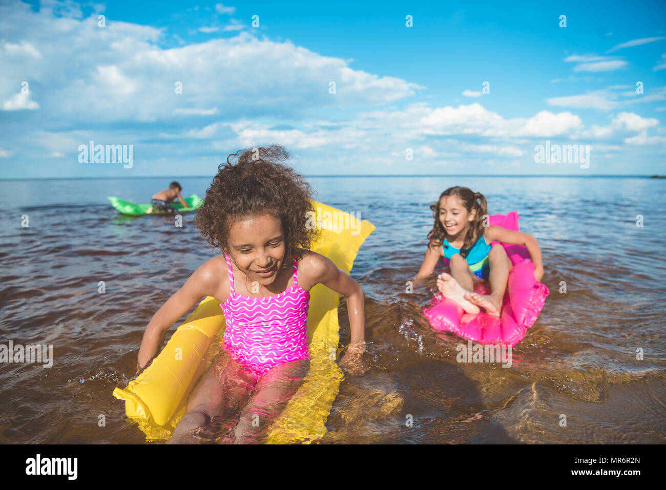 multicultural happy girls swimming on inflatable mattresses at sea together - Stock Image