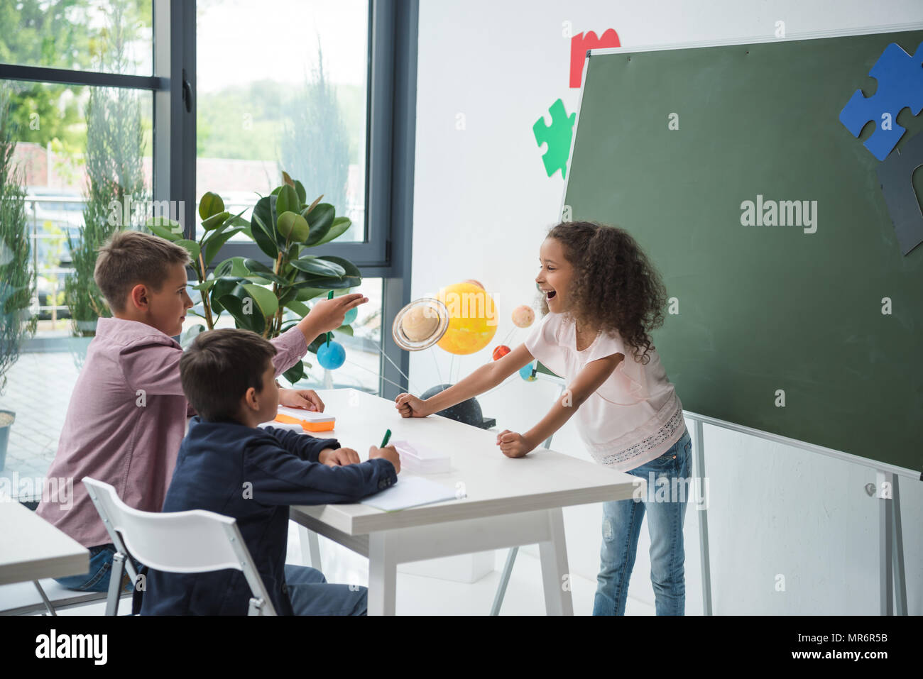 Adorable multiethnic schoolchildren talking and smiling at desk in classroom - Stock Image