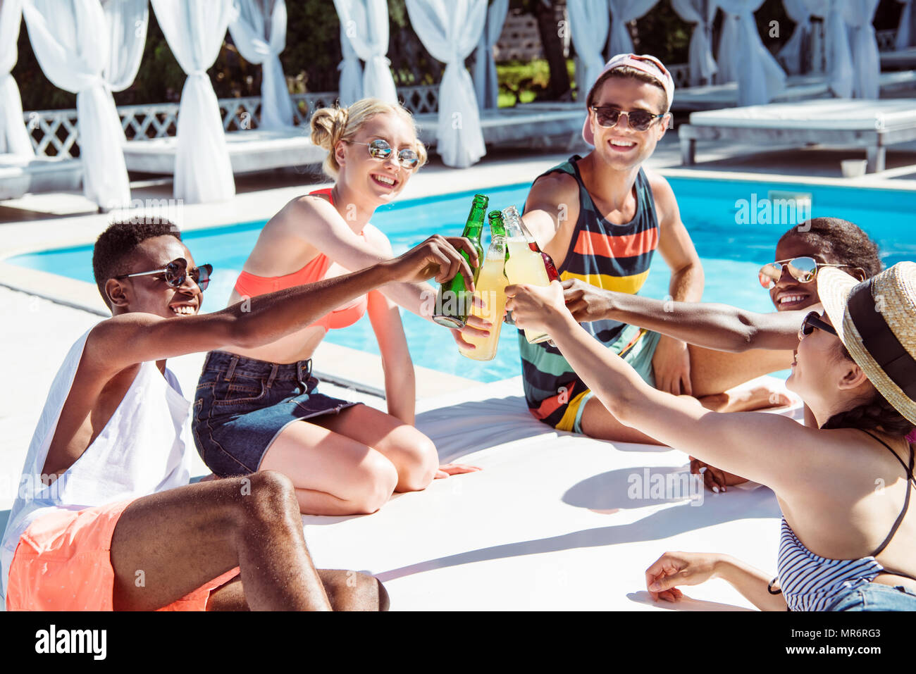 Group of young multiethnic friends clinking with beverages at poolside at resort - Stock Image
