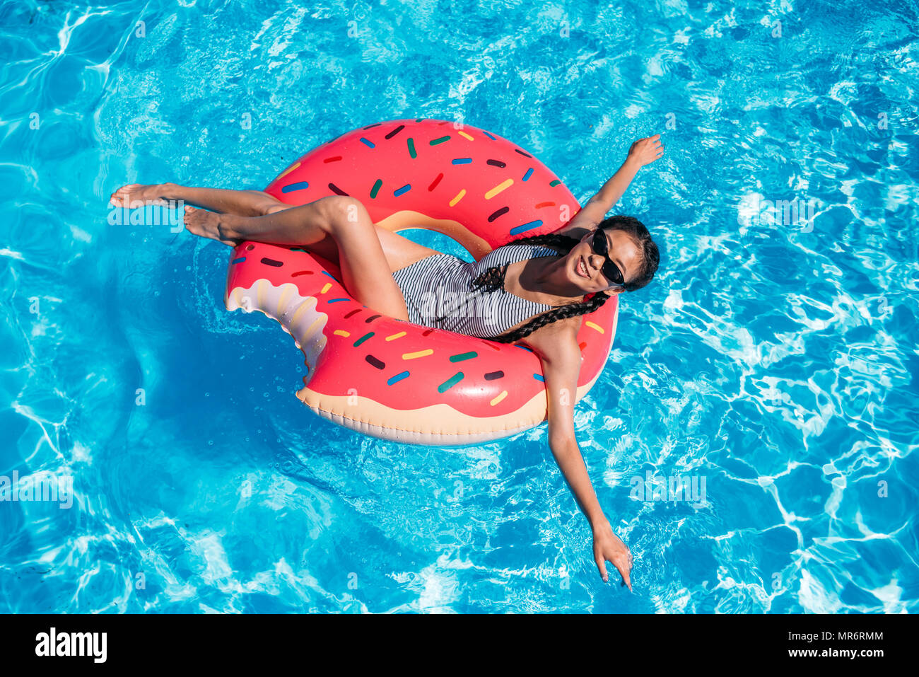 Young asian woman floating on inflatable donut in swimming pool - Stock Image