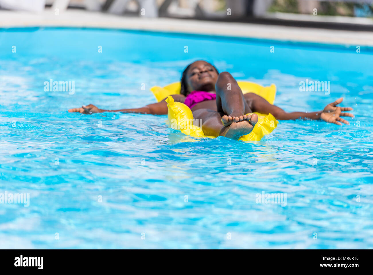 African american woman floating on inflatable mattress in swimming pool - Stock Image
