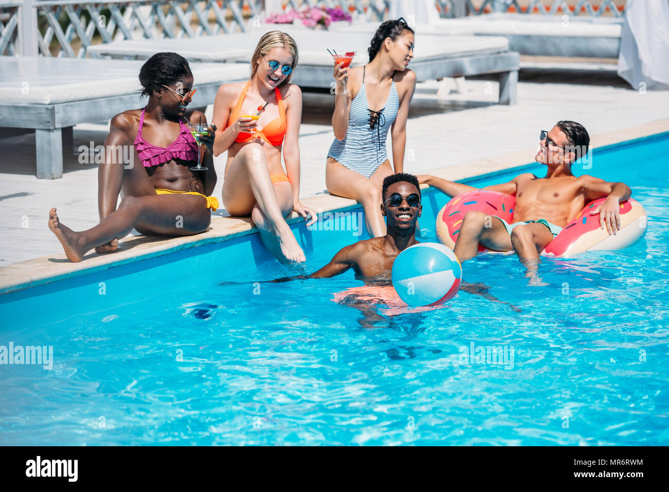 Group of young happy multiethnic people having fun together in swimming pool - Stock Image