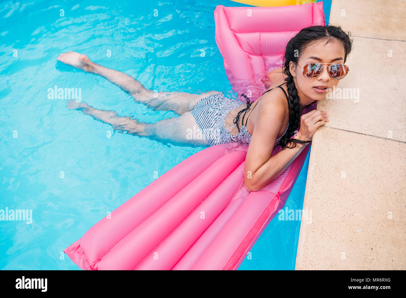 Young asian woman floating on inflatable mattress in swimming pool - Stock Image