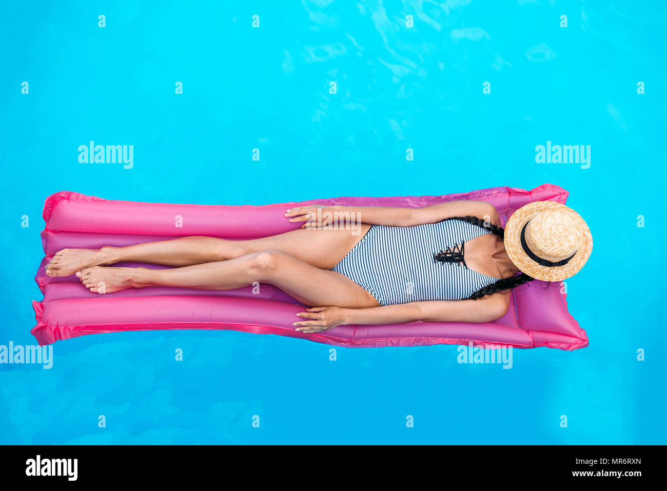 Young woman with straw hat covering face floating on air mattress in swimming pool - Stock Image
