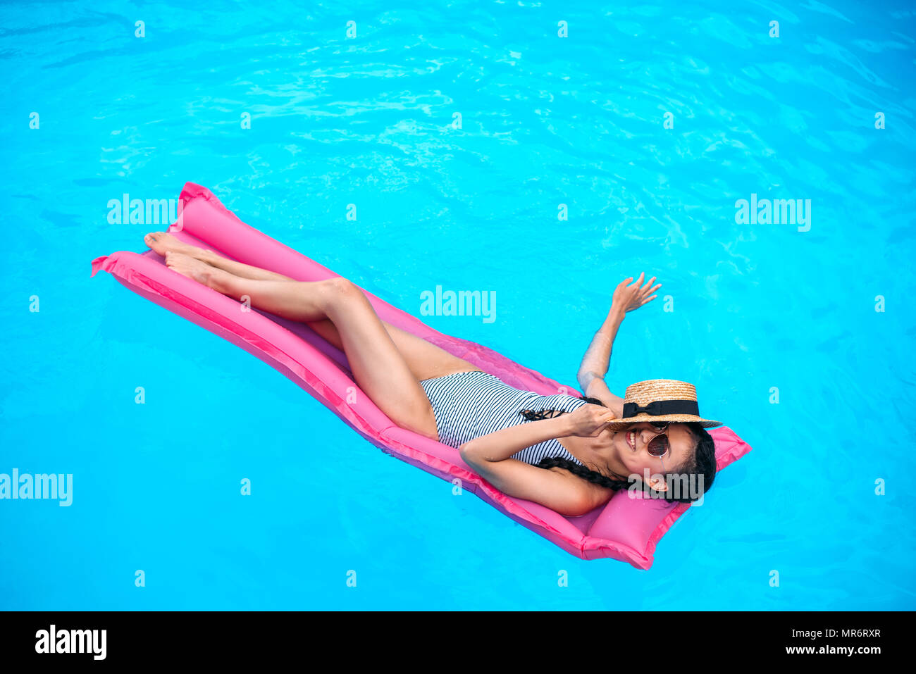 Young asian woman with straw hat covering face floating on inflatable mattress in swimming pool - Stock Image