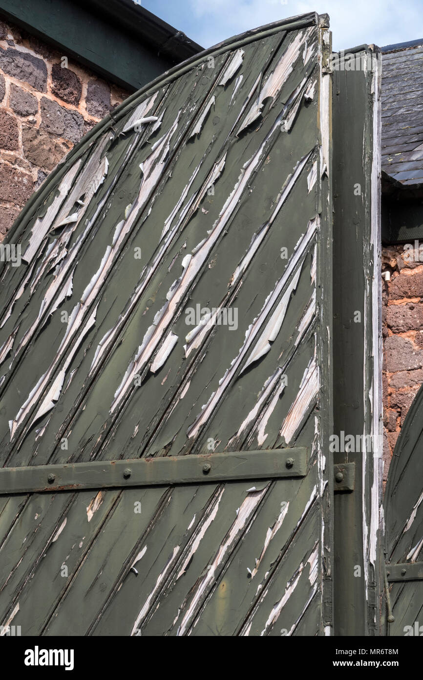 Peeling paint on some large oval topped doors gates - Stock Image