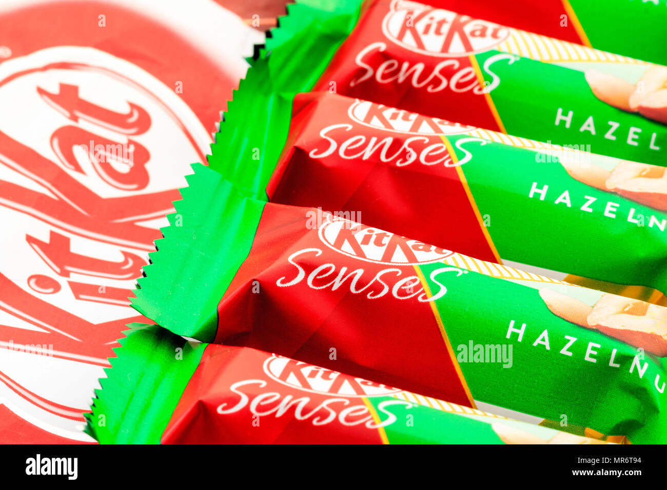 English Kitkat Senses Hazelnut packets lines up with a larger kitkat logo underneath and to the side. - Stock Image