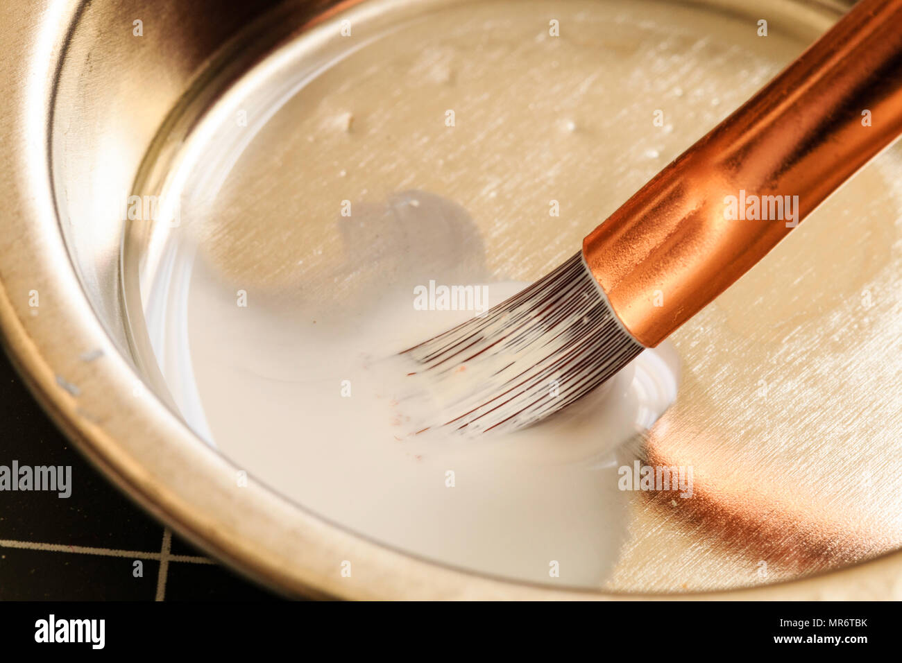 Small modeling paint brush in bowl being cleaned after use with paint thinner. Some blurred movement. Hairs of the brush soaked in liquid. - Stock Image