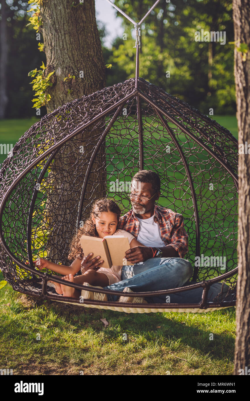 Little African American Granddaughter Reading Book While Sitting In  Swinging Hanging Chair With Grandfather