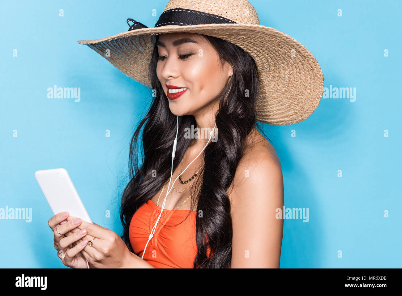 29694fbc46 beautiful asian woman in beach attire, listening to music in earbuds and  looking at smartphone