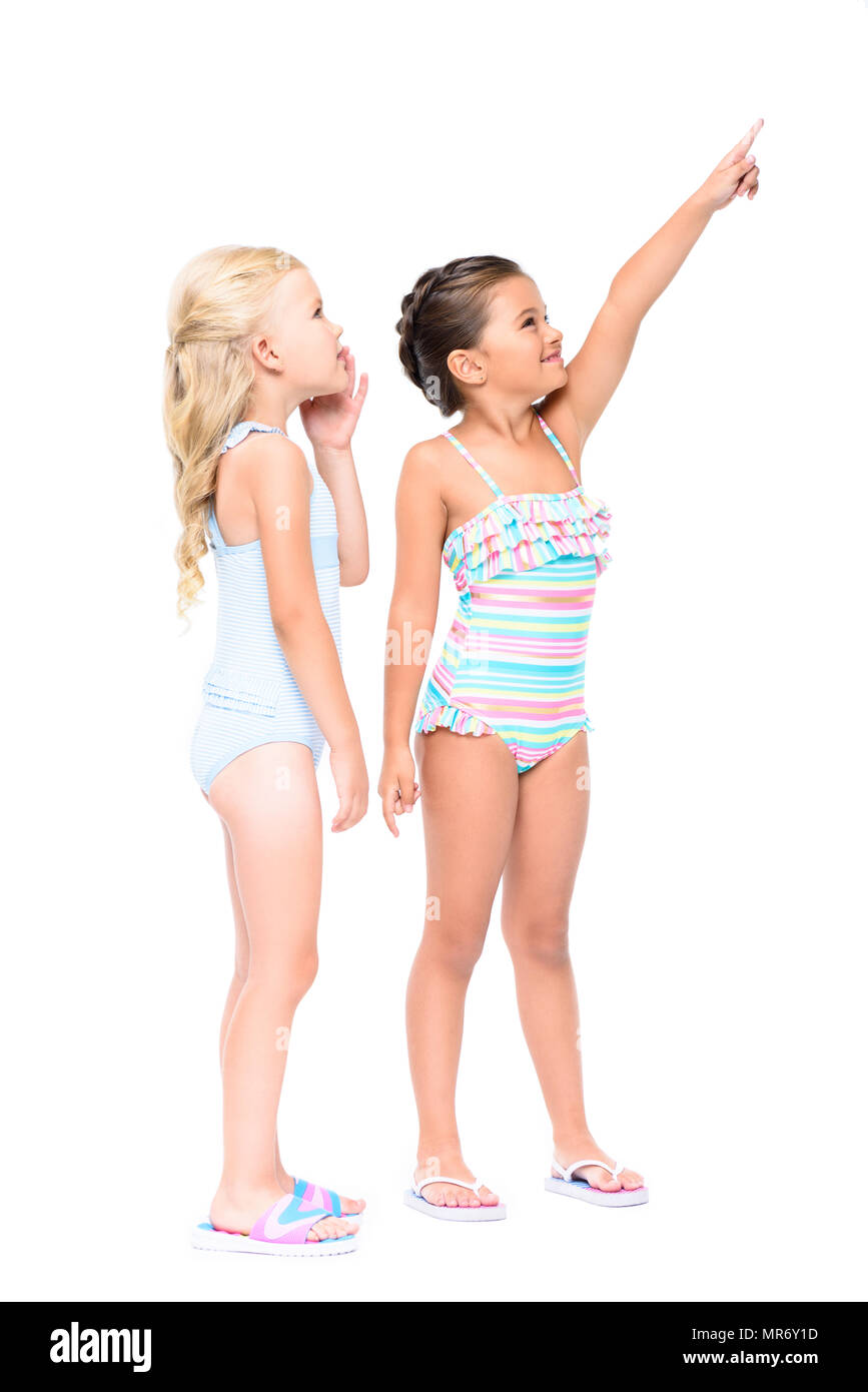 9184fbeb44 adorable little girls in swimsuits pointing with finger and looking away  isolated on white - Stock